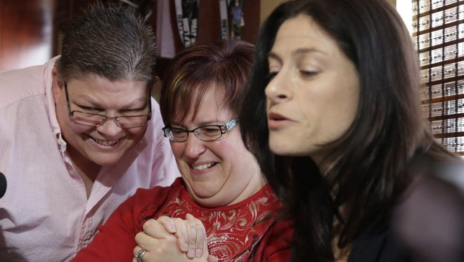 Jayne Rowse, left, and her partner, April DeBoer, react as their lawyer Dana Nessel reads a decision March 21, 2014, that Michigan's ban on same-sex marriage was ruled unconstitutional in Michigan.