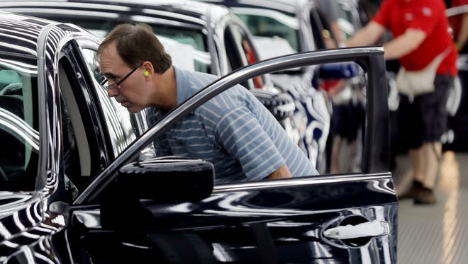 An employee at Nissan's Smyrna plant inspects finished vehicles as they come off the assembly line Feb. 26, 2018.