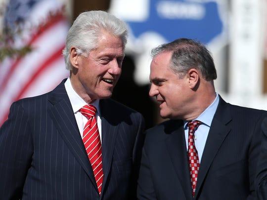 Former president Bill Clinton talks with Sen. Mark
