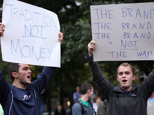 Ruben Rumbaut, left, a senior from Beverly Hills, and Ryan Graham, right, a Senior from Grosse Pointe Park, hold signs and chant during the Fire Dave Brandon rally on Tuesday, Sept. 30, 2014 at the University of Michigan in Ann Arbor.