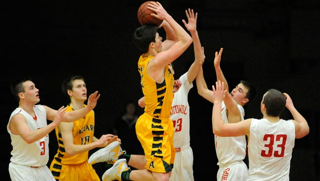 Kyle Monroe of Ashwaubenon gets airborne to sink the winning shot in overtime against Manitowoc Lincoln during their Fox River Classic Conference boys basketball game on Friday, Jan. 16, 2015 at Manitowoc Lincoln High School in Manitowoc.  Matthew Apgar/HTR Media