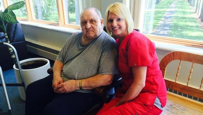 Mount View Care Center resident Roger Koenig sits next to Crystal Norenberg, a certified nursing assistant. Koenig thinks of Norenberg as a daughter.
