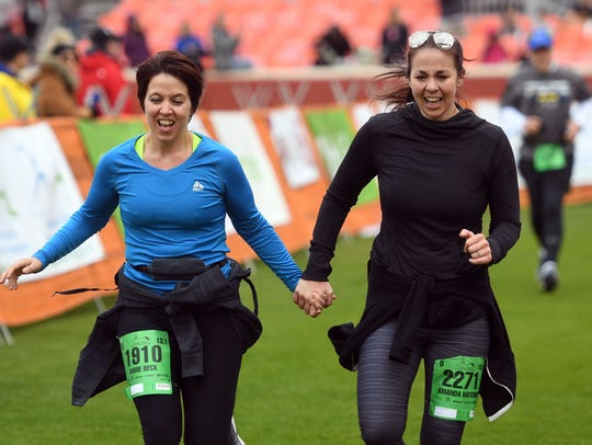 Marie Beck, left, and Jenna Humphreys cross the finish line together after completing the half-marathon in the Covenant Health Knoxville Marathon on Sunday.