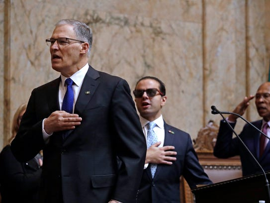 Gov. Jay Inslee, left, recites the Pledge of Allegiance