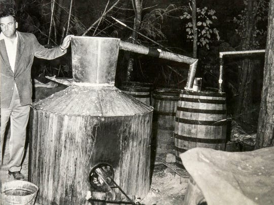 Sevier County Sheriff Ray D. Noland is shown with a confiscated moonshine still on June 6, 1956.