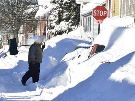 A man walks along a snowy East Washington Street on