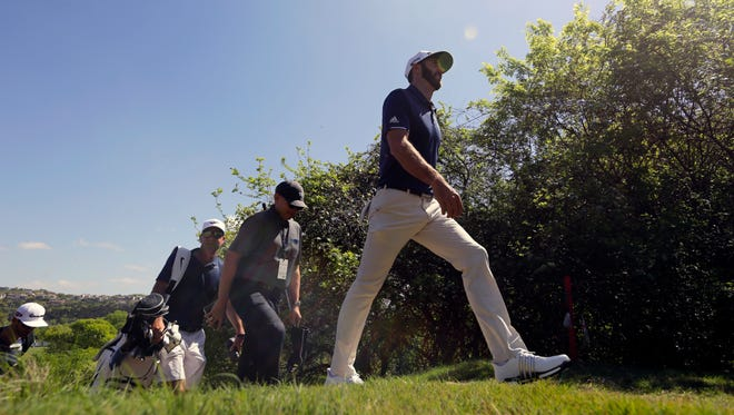 Dustin Johnson, right, walks to the 18th hole during a practice round for the Dell Match Play Championship golf tournament at Austin County Club, Tuesday, March 21, 2017, in Austin, Texas.
