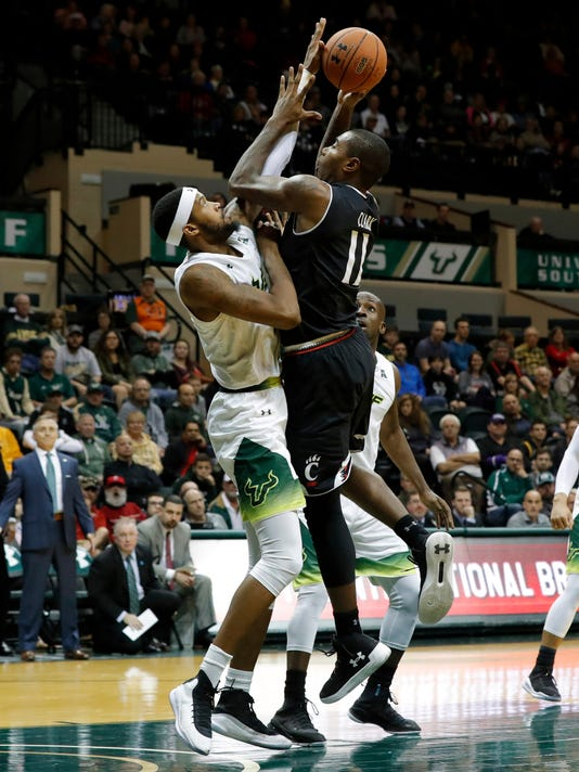 Cincinnati's Gary Clark, right, shoots over South Florida's Malik Martin, left, during the first half of an NCAA college basketball game Saturday, Jan. 13, 2018, in Tampa, Fla. (AP Photo/Mike Carlson)