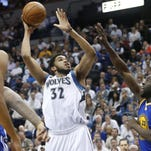 Minnesota Timberwolves Karl-Anthony Towns, left, shoots as Golden State Warriors Draymond Green, right, defends in the first quarter of an NBA basketball game Monday in Minneapolis.