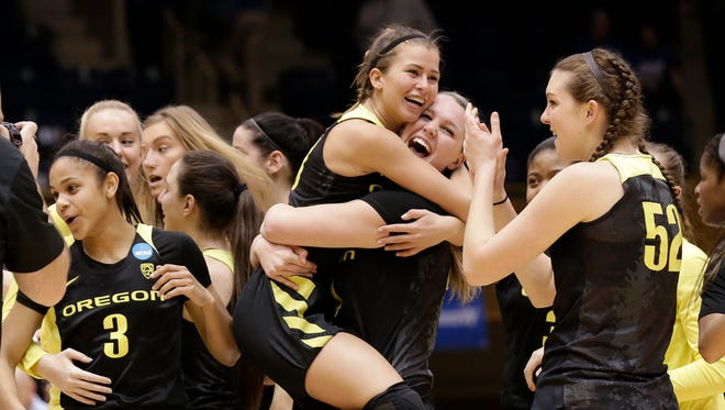 Oregon's Lexi Bando, center, jumps into the arms of Mallory McGwire as Sierra Campisano and Justine Hall (3) celebrate following a second-round game in the NCAA women's college basketball tournament in Durham, N.C., Monday, March 20, 2017. Oregon won 74-65.