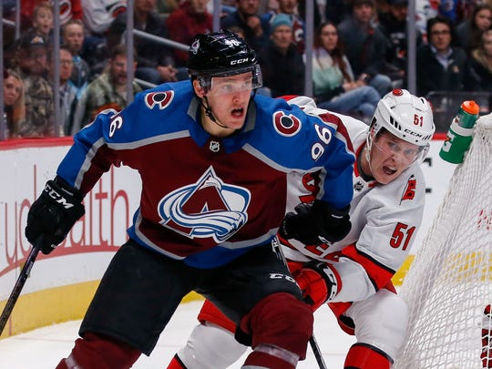 Dec 19, 2019; Denver, CO, USA; Colorado Avalanche right wing Mikko Rantanen (96) controls the puck ahead of Carolina Hurricanes defenseman Jake Gardiner (51) in the second period at the Pepsi Center. Mandatory Credit: Isaiah J. Downing-USA TODAY Sports