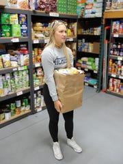 Hoisting a bag of food earmarked for a needy family