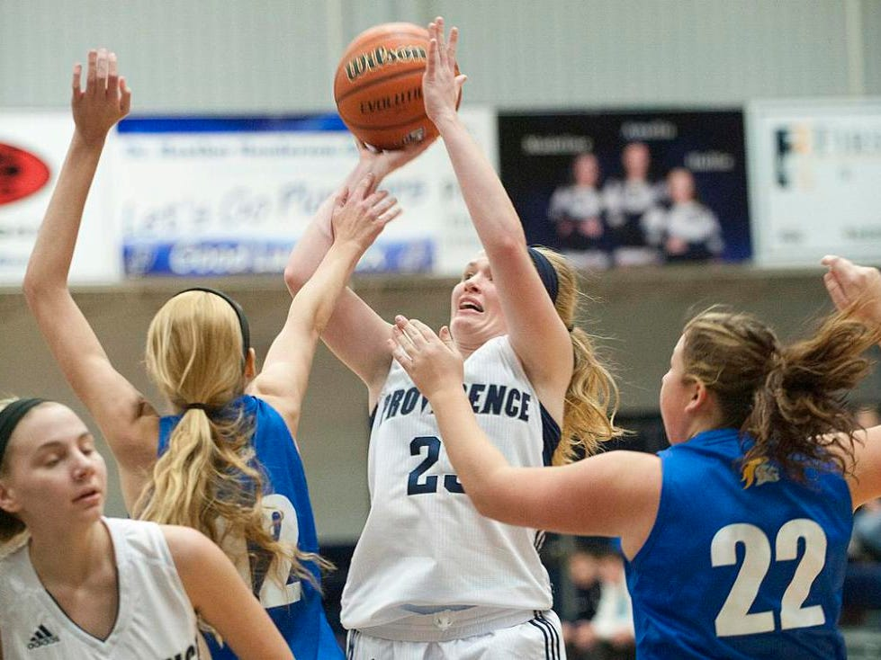 Providence Pioneers forward Claire Rauck shoots between defenders Chrisitan Academy of Indiana Lady Warriors center Brittany Moffett , left, and forward Cortney Baird, right. 16 December 2014