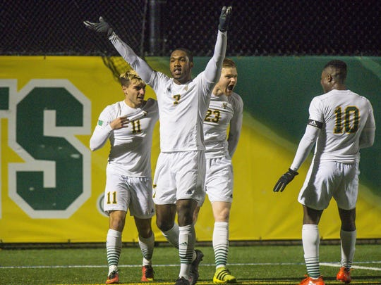 UVM's Brian Wright, center, celebrates his assist on a goal in the Catamounts' NCAA first-round win over Rider in November.