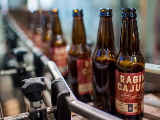 Bottles bearing the Ragin' Cajuns beer logo make their