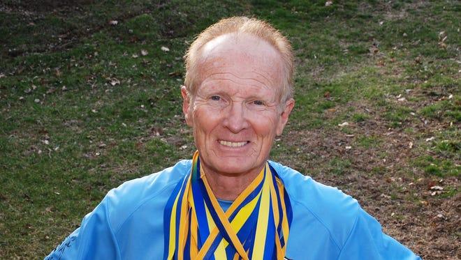 Doug White shows off some of his Boston Marathon medals.