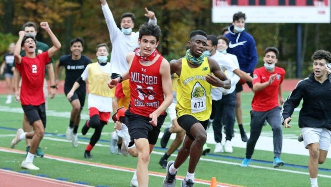 Milford High junior James Comisky (left) races past King Philip's Javon Joseph in a cross country meet on Wednesday at Milford High School. Comisky won the race as the Milford High boys soccer team watched the finish.