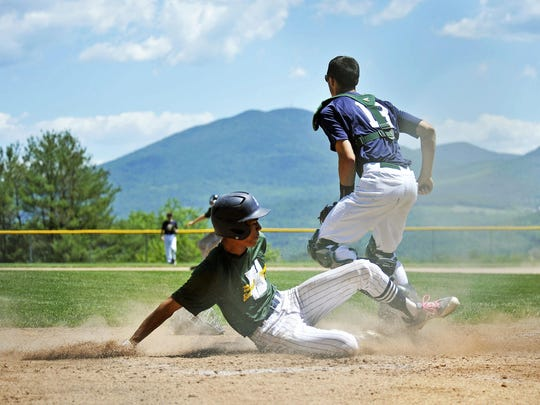 Essex's Elijah Baez scores a run with Burke Mountain as the backdrop during New Hampshire's 6-5 win over Vermont in Game 1 of the Twin State Classic at Lyndon State College on Saturday.