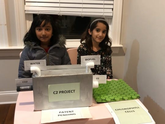 Mithra Menon and Eesha Nachnani show their C2 Project prototype, which would convert carbon dioxide into oxygen using artificial chlorophyll.