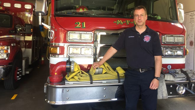 Mike Zyniecki, a Milwaukee firefighter, stands beside Engine 21.