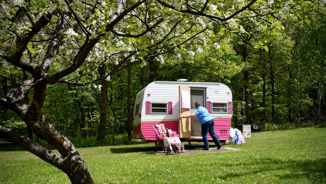 """Sue Notch opens the door of her camper Celia Rose Tuesday, May 17, at her home near Avon. Notch takes the 1965 camper on trips with Sisters on the Fly, an international """"glamping"""" organization."""