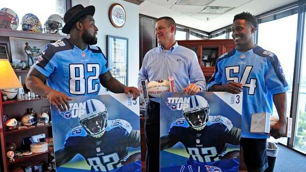 Titans players Delanie Walker, left, and Avery Williamson, right, pose for a photograph after they deliver a season ticket to Scott Ramsey Wednesday.