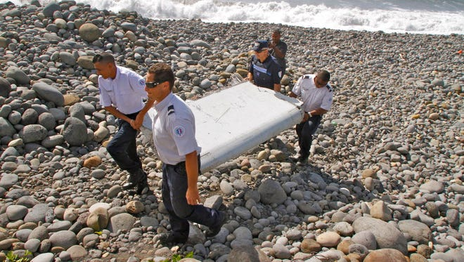 """French police officers carry a piece of debris from a plane in Saint-Andre, Reunion Island, on July 29, 2015. Air safety investigators, one of them a Boeing investigator, have identified the component as a """"flaperon"""" from the trailing edge of a Boeing 777 wing, a U.S. official said."""