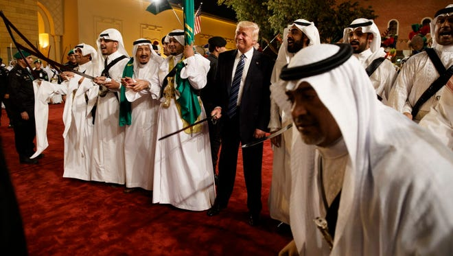President Trump holds a sword with traditional dancers on May 20, 2017, in Riyadh, Saudi Arabia.