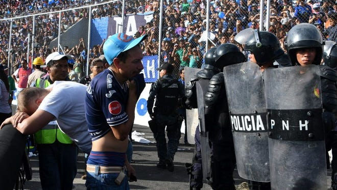 Two fans cry after supporters of Honduran team Motagua died in a stampede outside National Stadium in Tegucigalpa on May 28.
