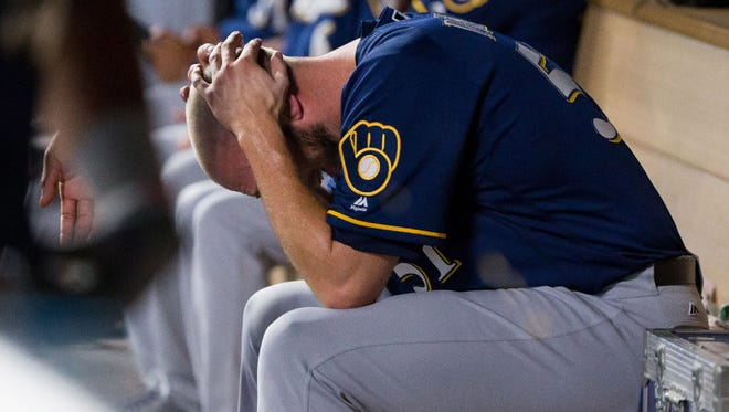 A despondent Oliver Drake sits in the Brewers dugout after allowing the Twins to score the tying and go-ahead runs in the bottom of the seventh. It was a balk by Drake that brought in the winning run for host Minnesota.