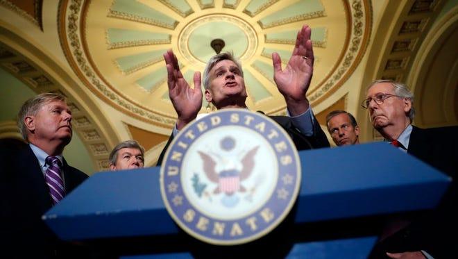 Sen. Lindsey Graham, left, and Sen. Bill Cassidy, center.