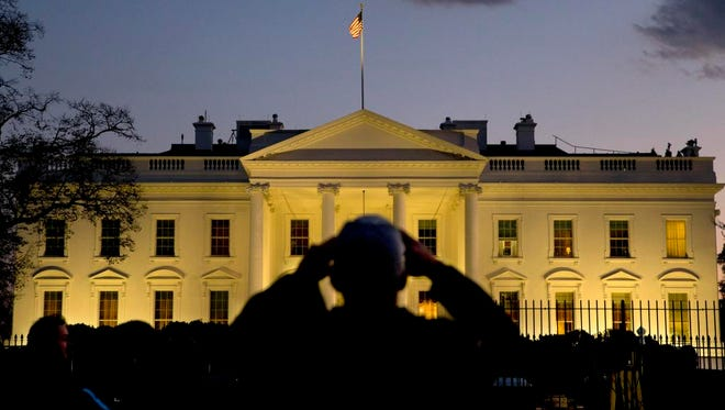 A man takes a cell phone photograph of the White House as dusk falls in Washington, Thursday, Nov. 20, 2014, hours before President Barack Obama is expected to announce steps he will take to shield millions of immigrants illegally in the United States from deportation. (AP Photo/Jacquelyn Martin)