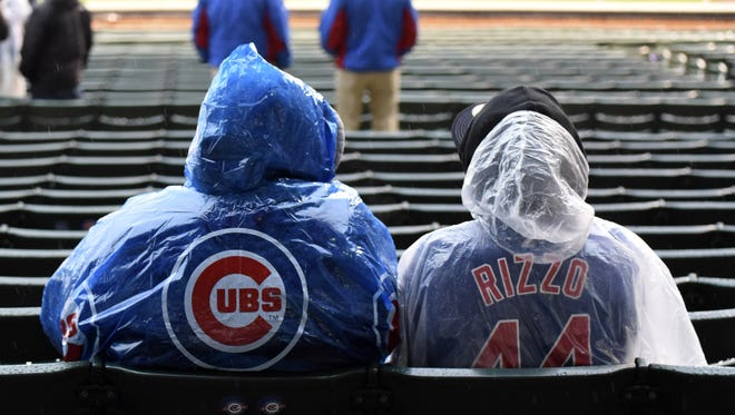 Fans sit in the stands before the Brewers-Cubs game was postponed by rain.
