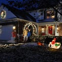 The Hidden Creek subdivsion in South Lyon is an optical feast during the holidays. Dennis Nagy, standing with son Ben in their decorated front yard, helps organize the 160-plus neighbors to do the same thing.