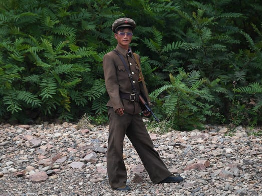 A North Korean soldier stands on the bank of the Yalu