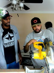 Don Milton Jr.,  works on cutting out a two-by-four from a wider piece of lumber with Michael McKissic in a Lansing house being renovated by McKissic's non-profit foundation.