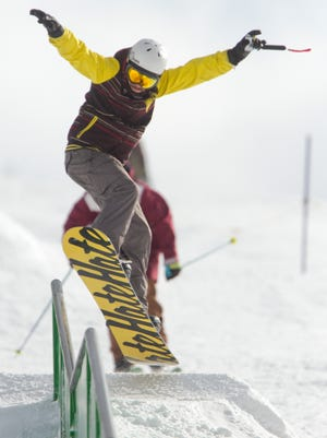 Detroit resident Benjamin Kehoe navigates the snowboard course at Mt. Brighton Saturday afternoon. Kehoe was among a strong number of skiers that took to the slopes with favorable weather at the local ski resort.