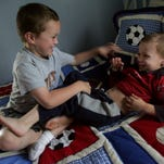 Cole, 3, Hawkins play on the bed in their room at their temporary home Friday, May 5, 2006 in Hendersonville, Tenn. Their mother Amy Hawkins threw herself over the children during the April tornado that destroyed their home. She is in Atlanta for physical therapy from her injuries which could prevent her from walking again.