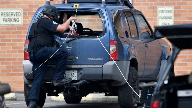 A Nashville Police bomb squad member investigates a car outside Burnette Chapel Church of Christ where shots were fired Sunday, Sept. 24, 2017, in Antioch, Tenn.