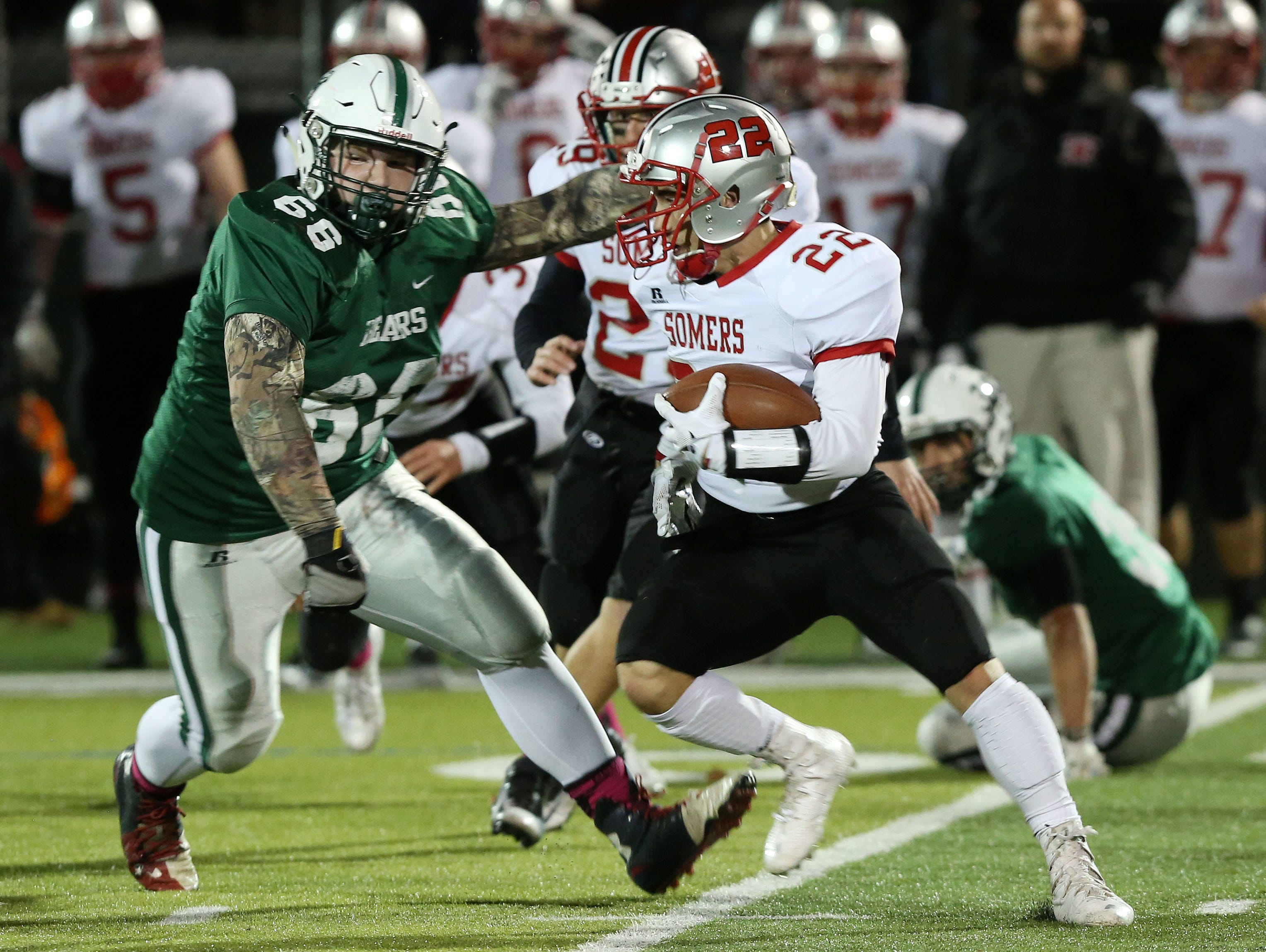 Somers' Vincent DiFilippo (22) tries to get away from Brewster's Nicholas Leahy (66) after recovering a first half fumble during the Section 1 Class A semifinals at Brewster High School Oct. 28, 2016.