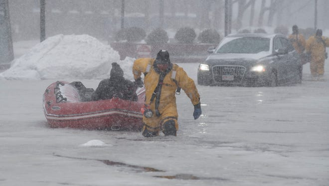 Firefighter Justin Plaza pulls a rescued motorist to dry land Thursday amid floods that accompanied a snowstorm in Boston.