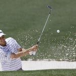 Bill Haas chips out of a bunker on the second green during the first round of the Masters golf tournament Thursday.