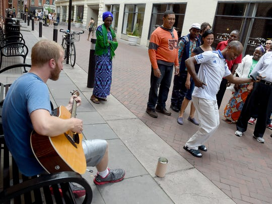 Kabulo Kambamaba of the Congo dances to the playing of a street musician while he and his ESL class from St. Mary's Church walk the streets of downtown Lancaster to practice their English.
