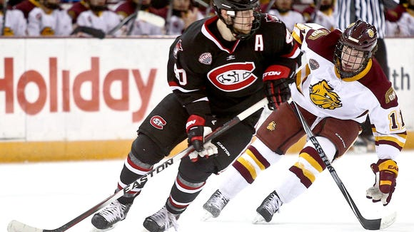Tim Daly of St. Cloud State controls the puck near Austin Farley (11) of Minnesota Duluth during Friday's game at Amsoil Arena in Duluth. Minnesota Duluth defeated St. Cloud State 4-2.