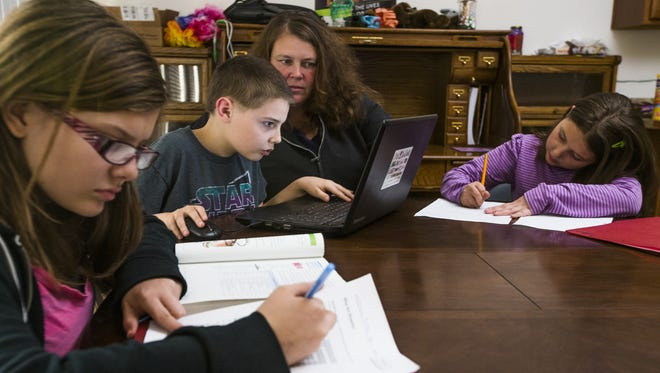 Kerry Thomas has eight children and three of them use Desert Choice Schools. They work on homework at home, Wednesday, December 9, 2015.  From left to right: Tatiana,15, James, 13, Kerry, and Anastasia, 11.
