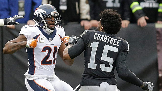 Denver Broncos cornerback Aqib Talib (21) fights Oakland Raiders wide receiver Michael Crabtree (15) during the first half of an NFL football game in Oakland, Calif., Sunday, Nov. 26, 2017.