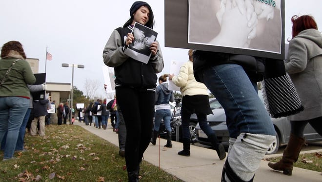 Demonstrators young and old rally in support of three young Brighton middle school student victims of sexual assault at the Livingston County Judicial Center Monday, Dec. 4, 2017.