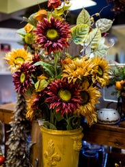 Flowers are displayed amongst fall items at Caroline