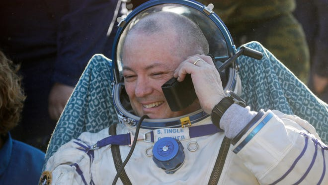 U.S. astronaut Scott Tingle speaks on the phone with relatives shortly after the landing of the Russian Soyuz MS-07 space capsule about 80 miles south-east of the Kazakh town of Zhezkazgan, Kazakhstan, June 3.