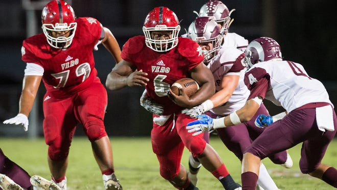 Vero Beach's Akeem Dixon (center) fights for extra yards at the end of a run in the first quarter as Riverview's Brantley Seadrow (right) and Julian Lowenstein (rear) try to stop him during the high school football Region 2-8A semifinal game Friday, Nov. 17, 2017, at Vero Beach High School.